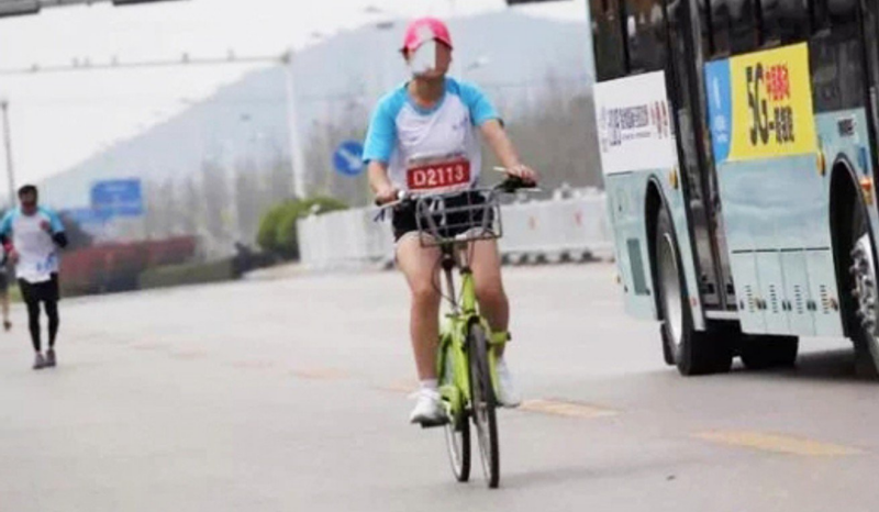 Escándalo en el maratón de Xuzhou: una corredora en bici y aficionados robando el avituallamiento